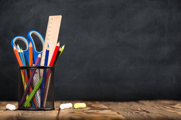 schreibtisch des schülers, bleistifte in metallhalter auf blackboard-hintergrund - kreide farbe schreibtisch stock-fotos und bilder