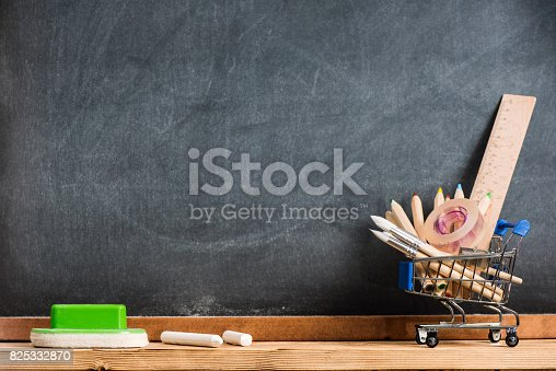 istock Desk Of Student, Pencils In Metal Shopping Holder On Blackboard Background 825332870