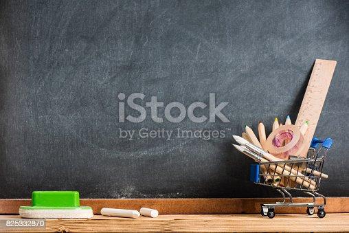 istock Desk Of Student, Pencils In Metal Shopping Holder On Blackboard Background 825332870