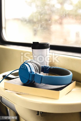 Desk table in train with headphones ,book and coffee