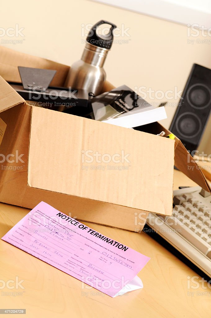 Desk with a notice of termination and a box of belongings stock photo