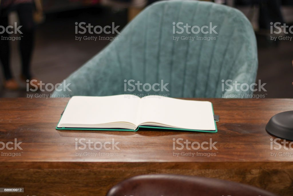 Desk with an open book on it and a material chair behind the desk royalty-free stock photo