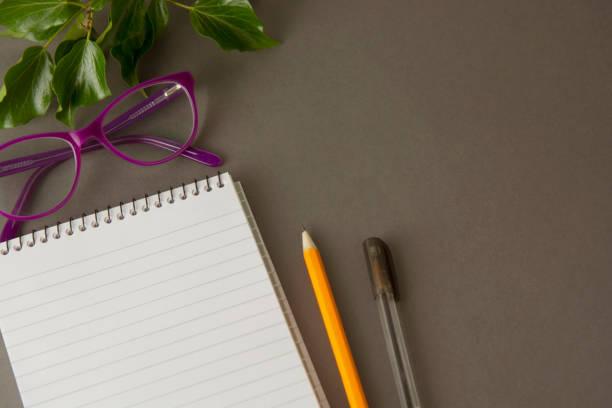 schreibtisch-arbeitsbereich, graue arbeitsbereich mit tasse kaffee, leeren notebook und pflanze auf dunklen tisch. tasse kaffee und platz für text. flach lag. kopieren sie raum. - küche deko blog stock-fotos und bilder