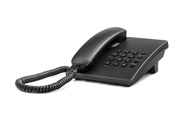 Desktop black phone with rounded buttons. Close-up.