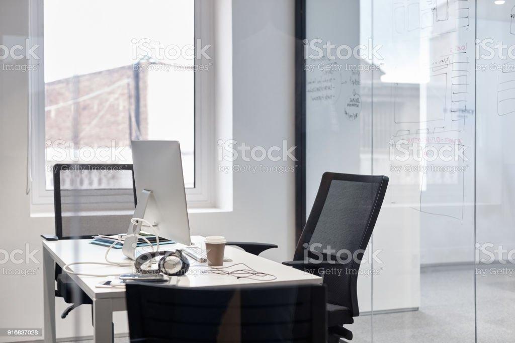 Desktop computer on desk. Empty chairs by glass window. It is in...