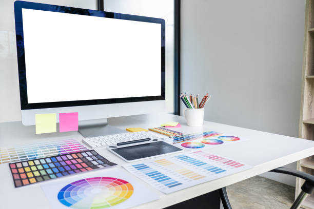 Desktop computer screen on white desk, Graphic designer and color swatch samples at workplace stock photo