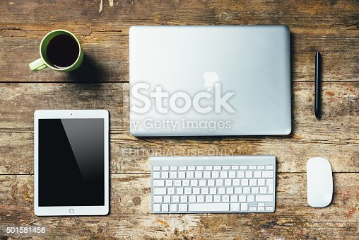Florence, Italy - December 14, 2015: Apple devices on a wooden desktop table. There are a Macbook Pro, an iPad an Apple Keyboard and a Magic Mouse, in addition to a cup of tea.
