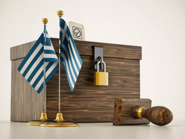 Desktop-Flaggen Griechenlands und Stempel stehen neben der Urne – Foto