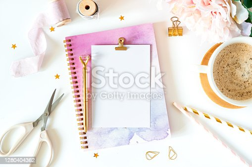 Desktop mock up, handmade DIY tools. Top view of white working table background with cup of coffee. Flat lay scissors, tapes, planner, golden paper binder clips, blank greeting card, Notebook and pen.