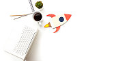 Directly above view of a laptop, notepad, model spaceship, flower and cup of coffee on pure white background. Representing desktop of a startup company.