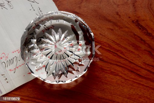 Cut crystal paperweight sits on handwritten note and wooden desk