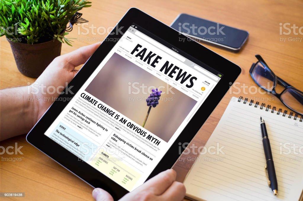 desktop tablet fake news stock photo