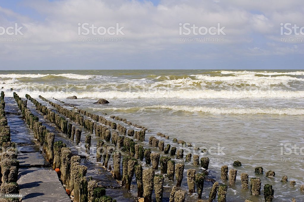 """Desolate break-water at the seaside """"Abandoned pier at the beach in the early afternoon.Location: Bredene, North Sea, Belgium."""" Abandoned Stock Photo"""