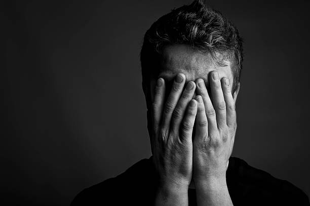 Despair Black and white portrait of a man with his head held in his hands. Copy space to the left. head in hands stock pictures, royalty-free photos & images