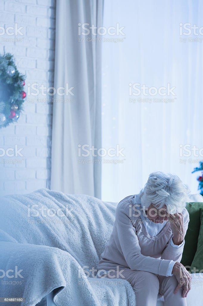 Despair senior woman on sofa stock photo