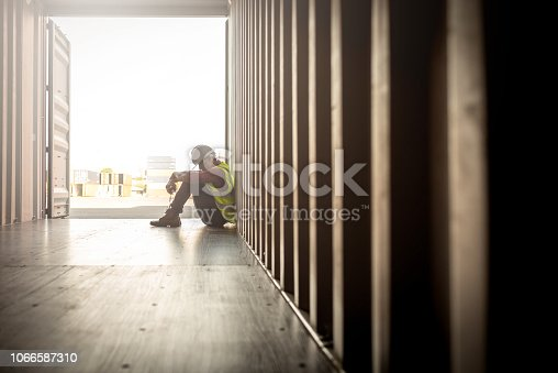 1001622522 istock photo despair staff in logistic business sittng in container 1066587310