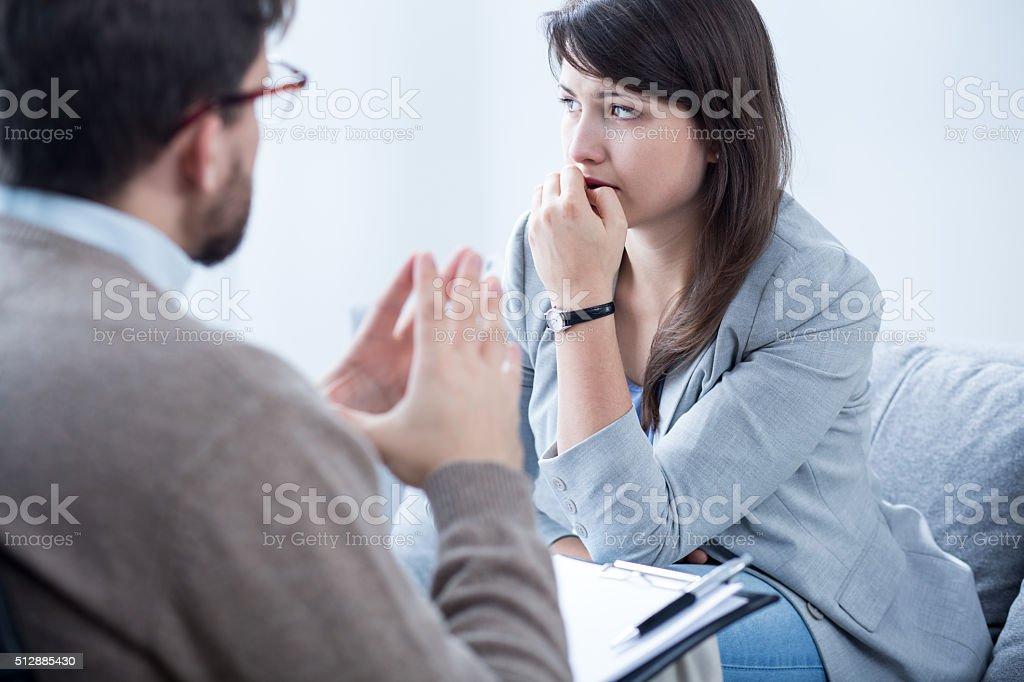 Despair woman biting her nails stock photo