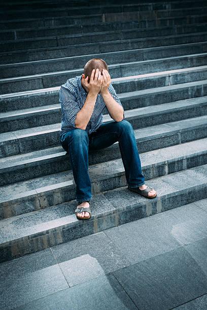 Verzweifelten Mann auf seinem Gesicht mit Händen sitzt auf Treppen – Foto