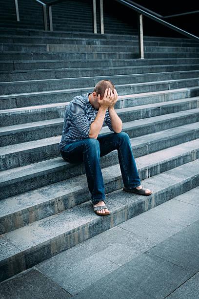 Verzweifelten junger Mann auf seinem Gesicht und Hände – Foto