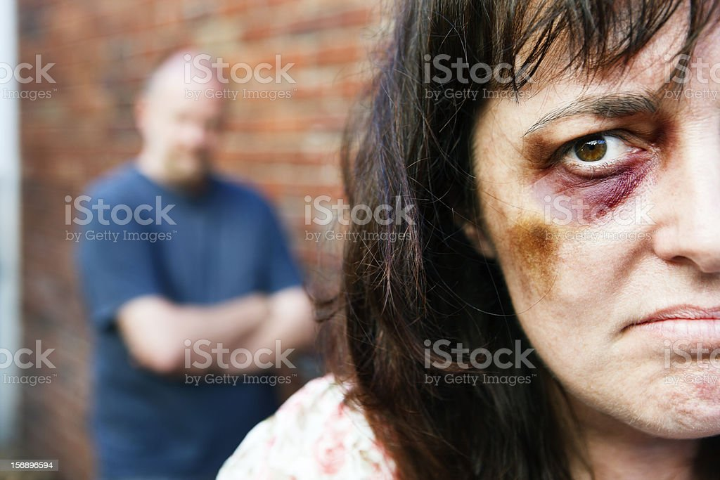 Despairing battered woman with threatening male in background stock photo