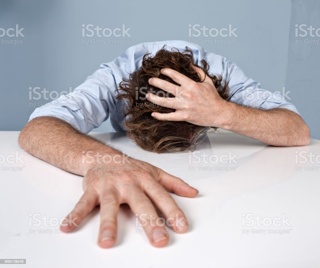 A man at the end of his tether has collapsed onto his desk, clutching...