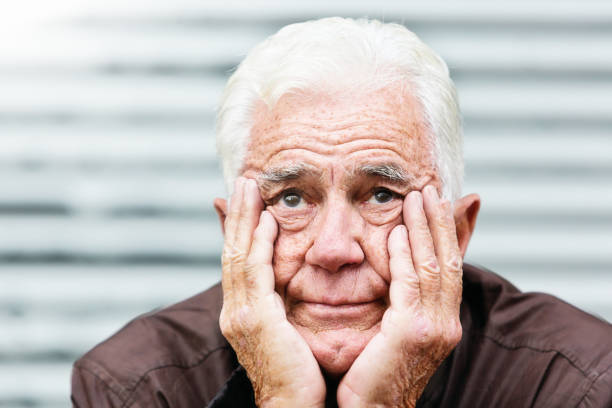 Despairing old man, head in hands, looks at camera stock photo