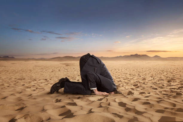 Desparate businessman hiding head in the sand stock photo