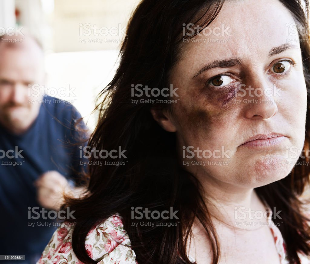 Desperate abuse victim with threatening clenched-fist man behind her stock photo
