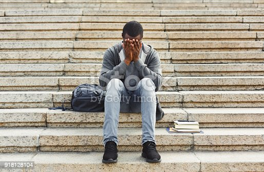 istock Desperate african-american student sitting on stairs outdoors 918128104