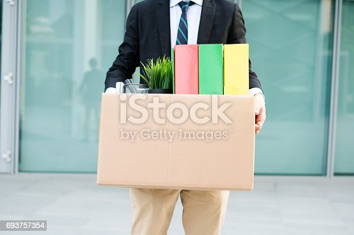 istock Desperate and fired businessman walking away from office 693757354