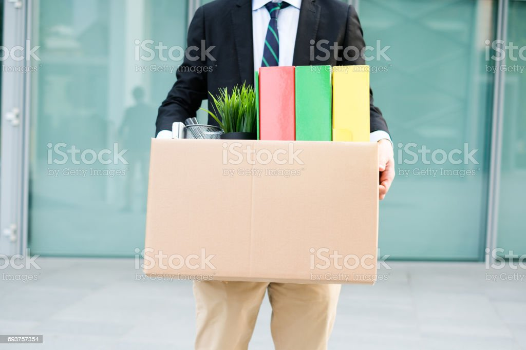 Desperate and fired businessman walking away from office stock photo
