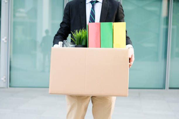 Desperate and fired businessman walking away from office - foto stock