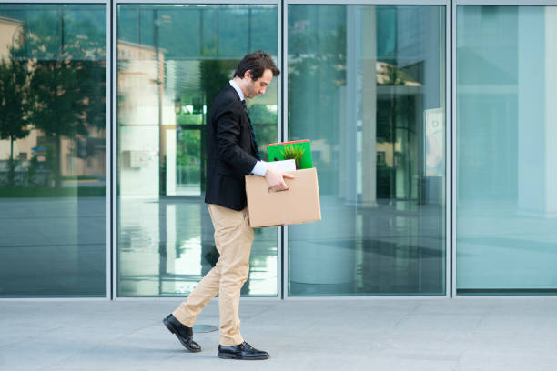 Desperate and fired businessman walking away from office Sad fired businessman taking away his belongings from the financial district downsizing unemployment stock pictures, royalty-free photos & images