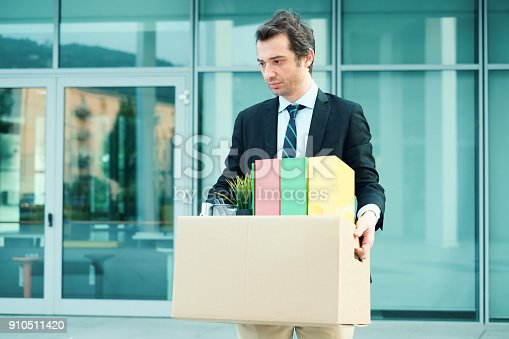 1181817161 istock photo Desperate and fired businessman walking away from office 910511420