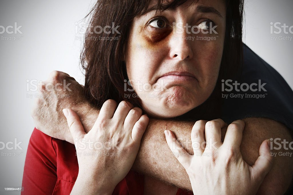 Desperate battered woman tries to break away from attacking man stock photo