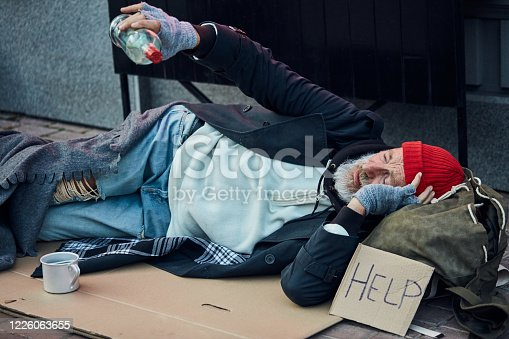 Pitiable dirty bum with sign of help, lie on floor, holding empty bottle of alcohol. Beggar in old clothes in cold weather
