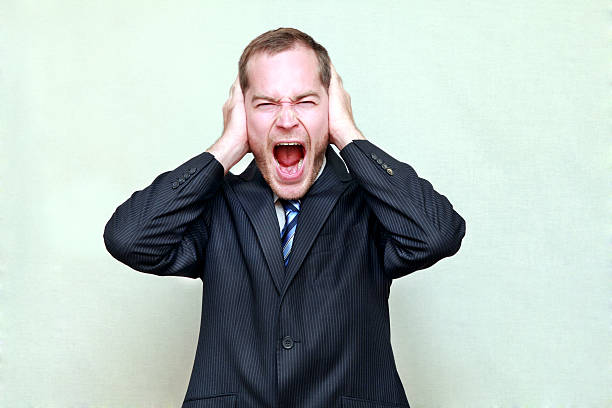 Desperate businessman clutches his head stock photo
