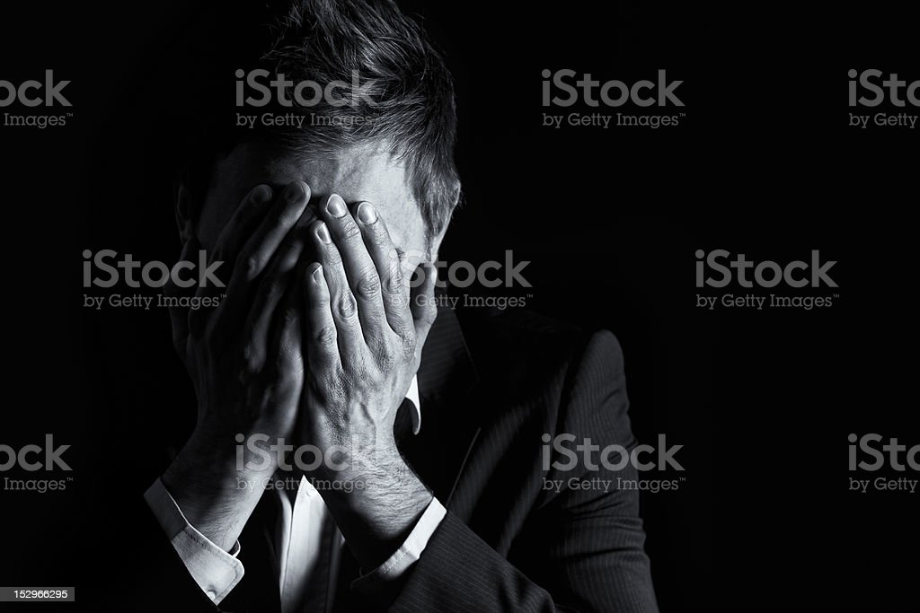 Desperate businessman covering his face. stock photo