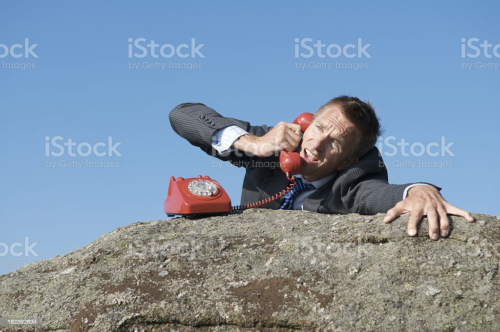Desperate Businessman On the Phone Call from Rock Cliff stock photo