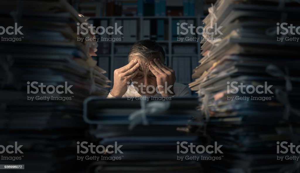 Desperate businessman working late stock photo