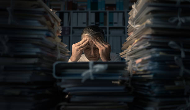 Desperate businessman working late Desperate businessman working in the office late at night and overloaded with work, his desktop is covered with paperwork: business management and deadlines concept overworked stock pictures, royalty-free photos & images