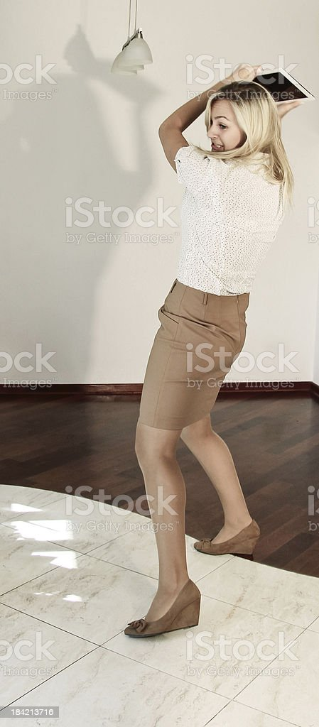 Desperate businesswoman throwing tablet royalty-free stock photo