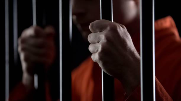 Desperate criminal holding jail bars feeling regret for committing crime closeup stock photo
