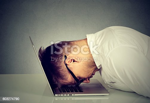 istock Desperate employee stressed man resting head on laptop 603274790