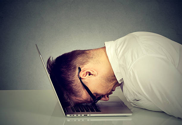 Desperate employee stressed man resting head on laptop Desperate employee, stressed young man resting head on laptop keyboard mental burnout stock pictures, royalty-free photos & images