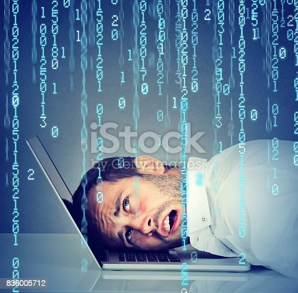 istock Desperate employee, stressed man resting head on laptop with binary code falling down 836005712