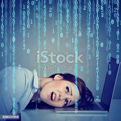 istock Desperate employee, stressed woman resting head on laptop with binary code falling down 836004958