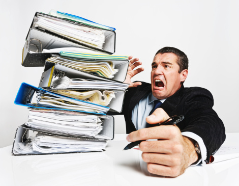A frantic executive tries desperately to prevent a huge and toppling pile of files from completely overwhelming him. A clear case of overwork causing businessman's burnout!