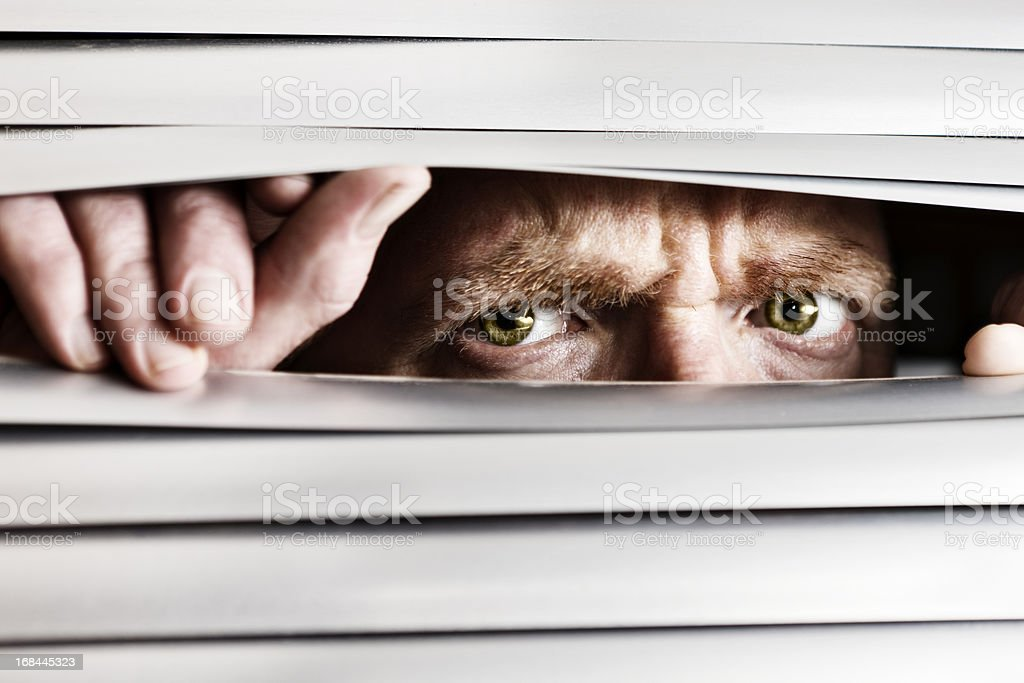 Desperate frowning man peeping out through venetian blinds stock photo