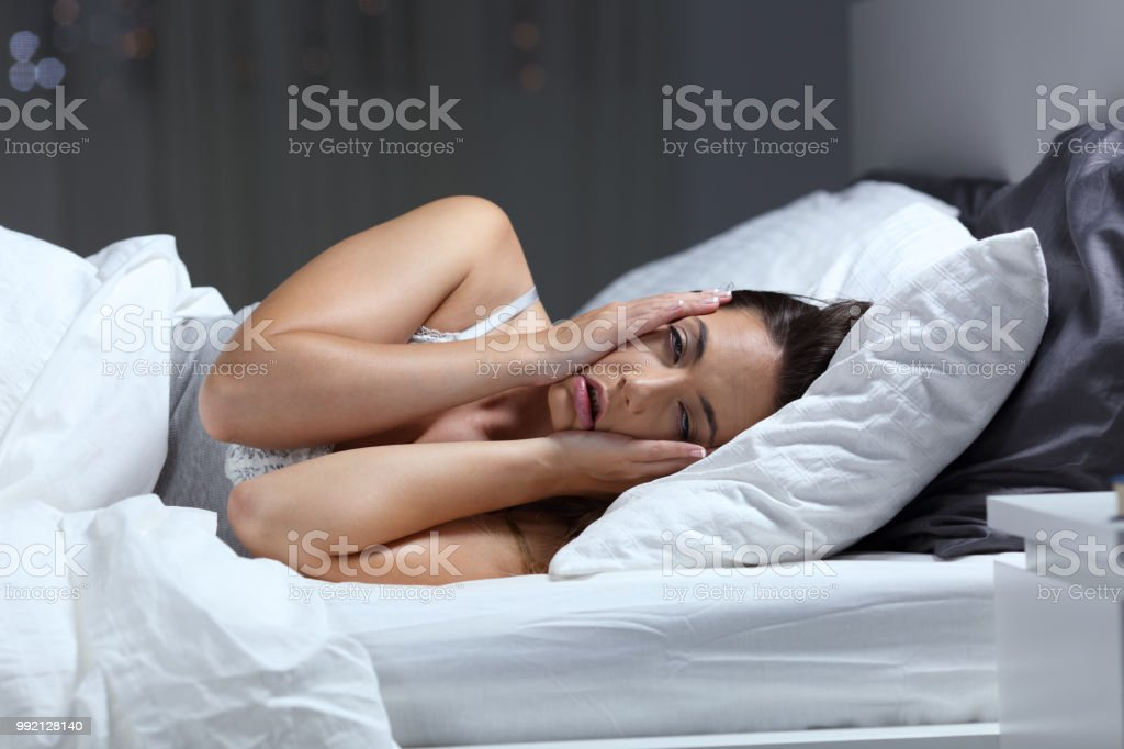 Desperate girl suffering insomnia trying to sleep stock photo